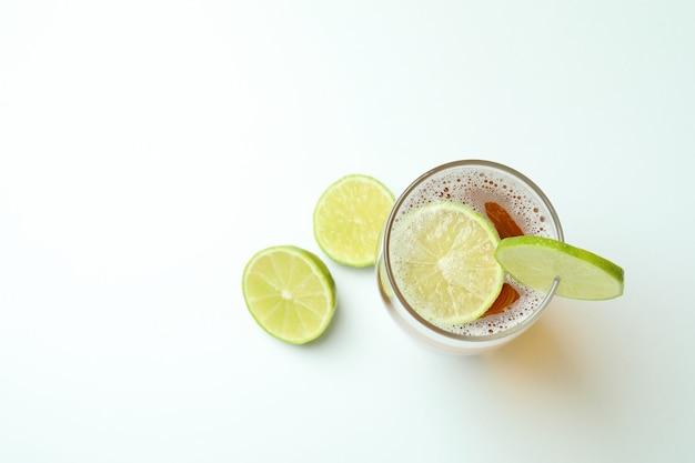 Szklanka piwa z limonką na białym tle