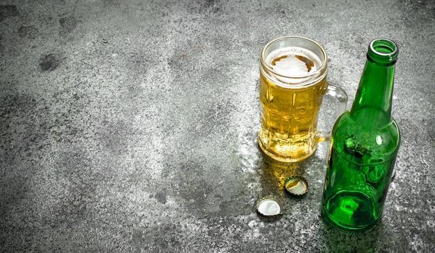 Szklanka piwa z otwieraczem do butelek i korkami. na rustykalnym stole.