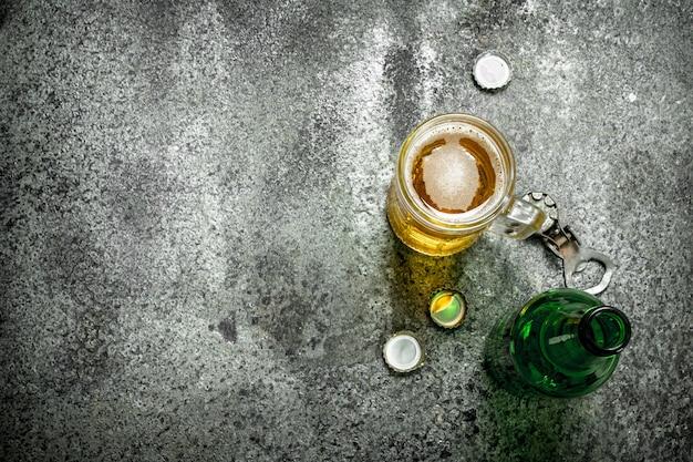 Szklanka piwa z otwieraczem do butelek i korkami na rustykalnym tle