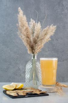 Szklanka piwa z rybą i plasterkami cytryny.