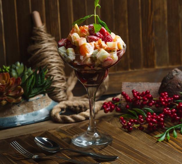 Szklanka plasterków owoców ozdobiona kremowym sosem i liśćmi mięty