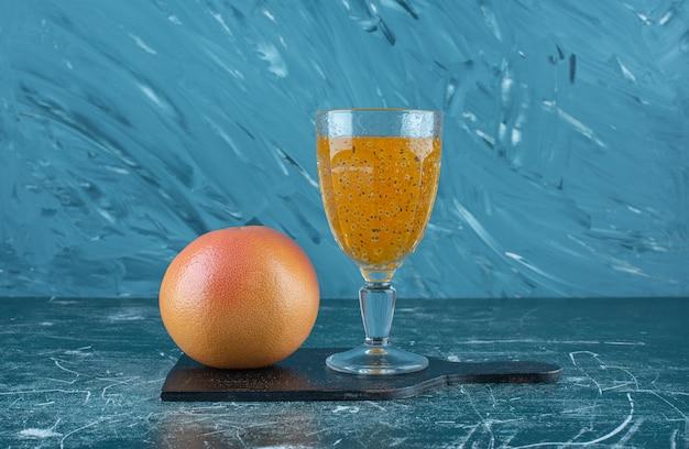 Szklanka przetworzonego soku i grejpfruta na niebieskim tle. wysokiej jakości zdjęcie