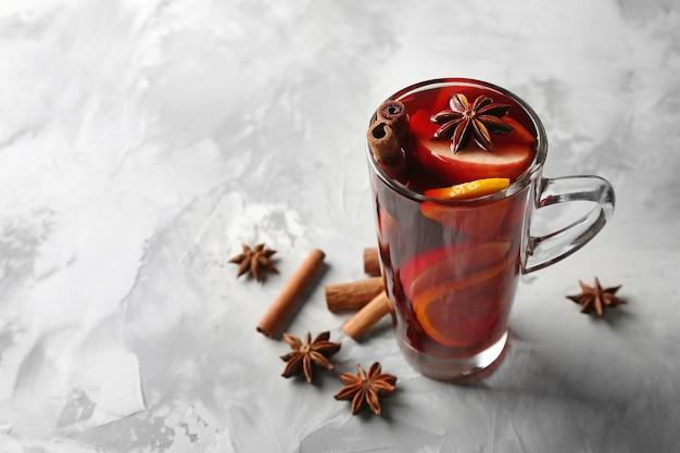 Szklanka pysznego grzanego wina bożonarodzeniowego na szarej powierzchni