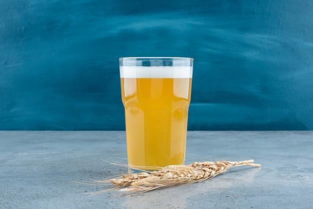 Szklanka pysznego piwa i pszenicy na szarym tle. zdjęcie wysokiej jakości