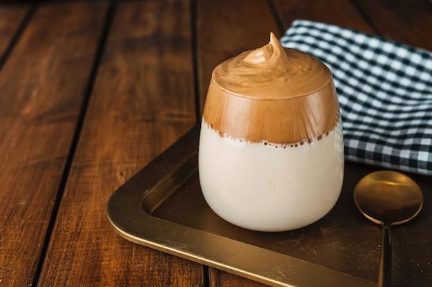 Szklanka pysznej pienistej i kremowej modnej kawy dalgona na złotej tacy