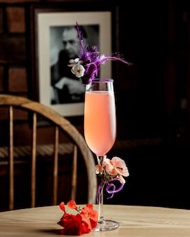 Szklanka różowego napoju ozdobiona kwiatami