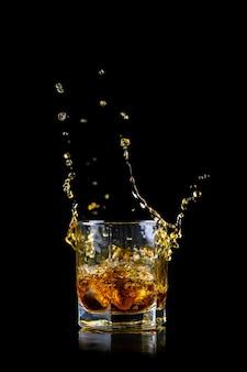 Szklanka rozpryskiwania whisky lub innego alkoholu z kostką lodu na czarnym tle