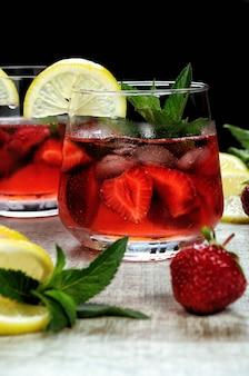 Szklanka schłodzonej lemoniady truskawkowej, listki mięty, plasterek cytryny z lodem