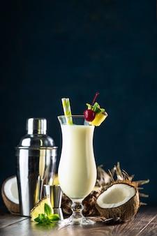 Szklanka smacznego mrożonego pina colada tradycyjny karaibski koktajl ozdobiony plasterkiem ananasa i wiśni
