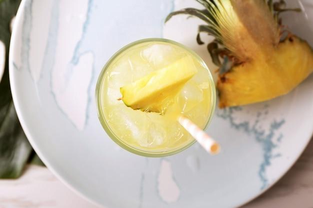 Szklanka smacznego świeżego soku ananasowego na talerzu, widok z góry