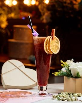 Szklanka smoothie przyozdobiona suszonymi pomarańczowymi plasterkami