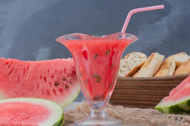 Szklanka smoothie z arbuza i kosz chleba na białym stole.