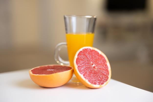 Szklanka soku cytrusowego i pokrojone połówki grejpfruta na białym stole
