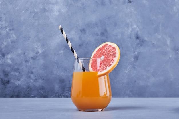 Szklanka soku grejpfrutowego na środku.