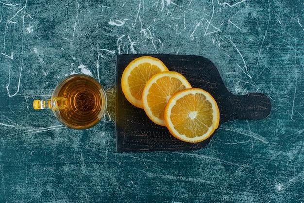 Szklanka soku gruszkowego i plasterki pomarańczy na desce do krojenia, na niebieskim stole.