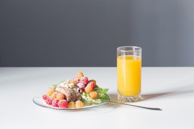 Szklanka soku i deseru jagody na białym stole