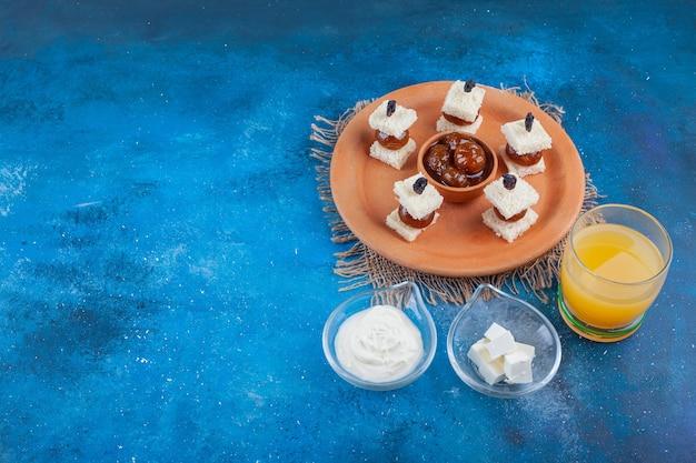 Szklanka soku i dżem figowy na talerzu obok misek sera na niebieskim stole.