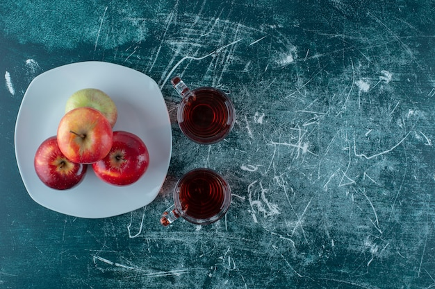 Szklanka soku jabłkowego i jabłko na talerzu, na marmurowym tle.