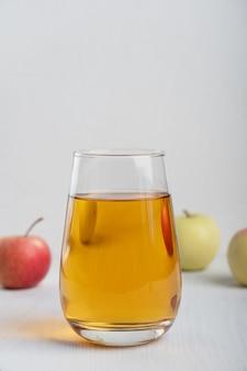 Szklanka soku jabłkowego stojąca na białych drewnianych stołach otoczona surowymi owocami