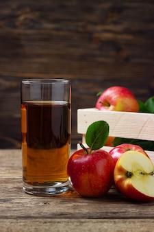 Szklanka soku jabłkowego z czerwonymi jabłkami na drewnianym stole