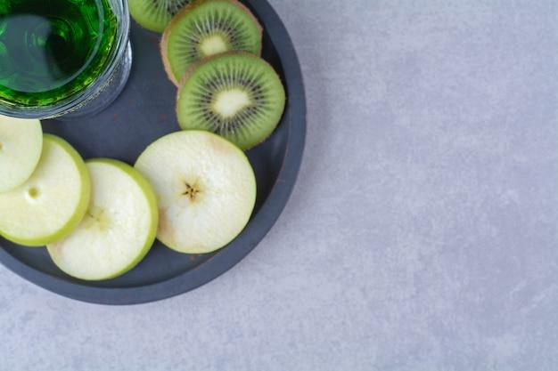 Szklanka soku kiwi, kiwi i jabłko na patelni, na marmurowym tle.