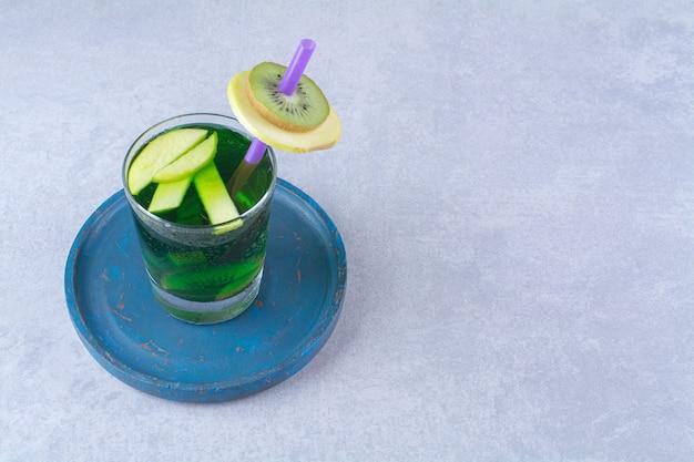 Szklanka soku kiwi na drewnianym talerzu, na marmurowym stole.