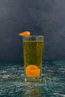 Szklanka soku mandarynkowego na marmurowym stole.