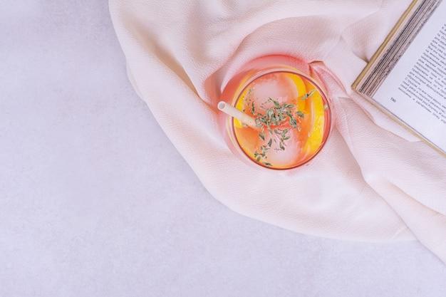 Szklanka soku na białej powierzchni z cytrynami