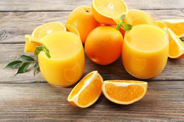 Szklanka soku pomarańczowego i plastry na powierzchni drewnianego stołu