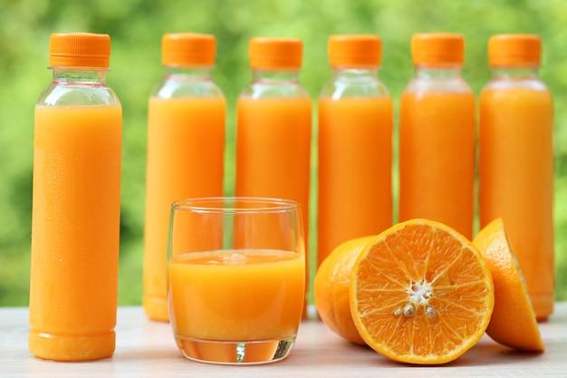 Szklanka soku pomarańczowego i pomarańczy na naturalnej zieleni