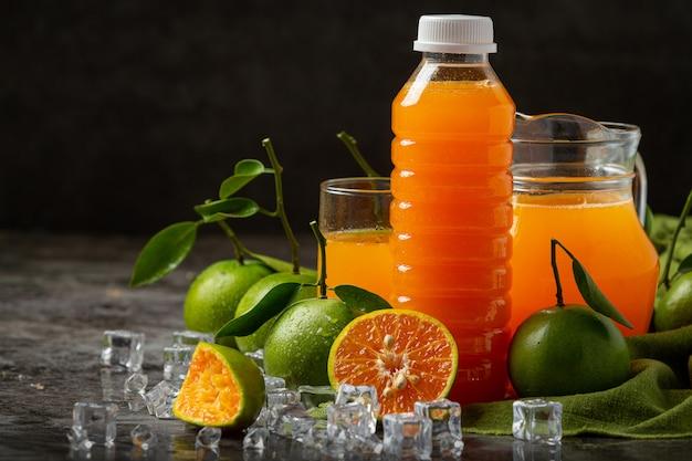 Szklanka soku pomarańczowego i świeżych owoców na podłodze z kostkami lodu.