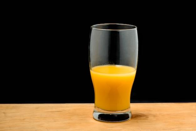 Szklanka soku pomarańczowego na drewnianym biurku