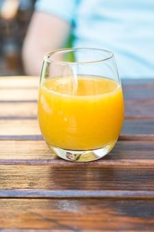 Szklanka soku pomarańczowego na drewnianym stole w ulicznej kawiarni
