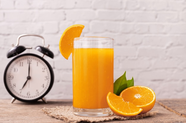 Szklanka soku pomarańczowego na drewnianym stole.