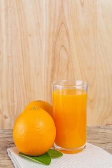 Szklanka soku pomarańczowego umieszczonego na drewnie.