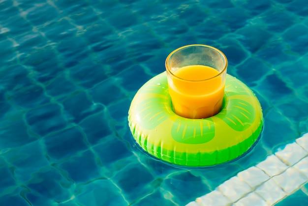 Szklanka soku pomarańczowego z pierścieniem pływać przy odkrytym basenie