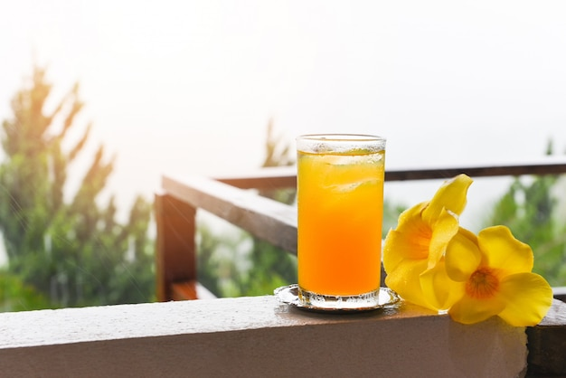 Szklanka soku pomarańczowego z żółtym kwiatem na balkonie z kroplami deszczu rano