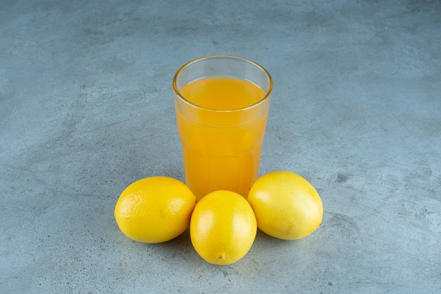 Szklanka soku pomarańczowego ze świeżymi cytrynami.