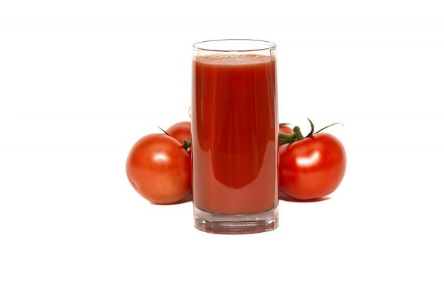 Szklanka soku pomidorowego i czerwonych, dojrzałych pomidorów na liściu świeżej sałaty, na białym tle