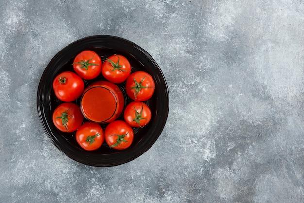 Szklanka soku pomidorowego na czarnym talerzu.