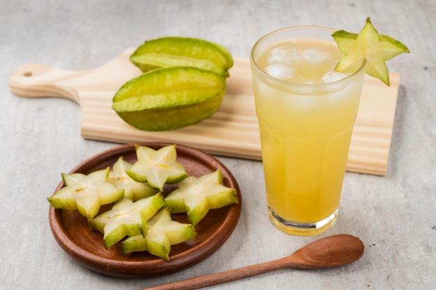 Szklanka soku starfruit z lodem i plasterkami owoców.