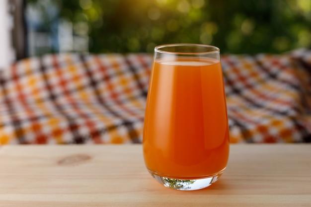 Szklanka soku w ogrodzie. drewniany stół.