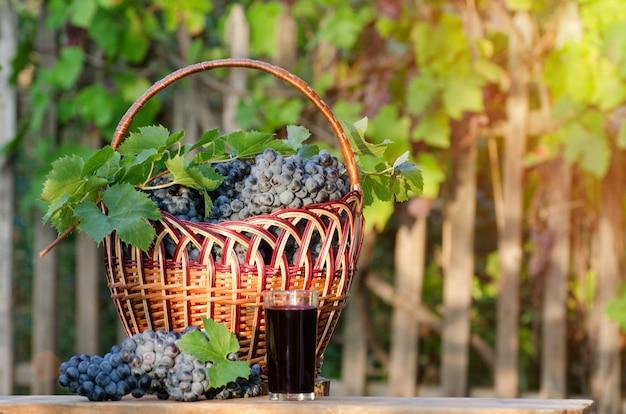 Szklanka soku winogronowego z winogron wiklinowym koszu