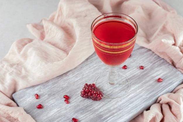 Szklanka soku z granatów ze świeżymi nasionami na drewnianej desce