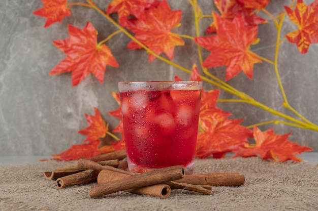 Szklanka soku z kawałkami owoców, liśćmi i laskami cynamonu na płótnie