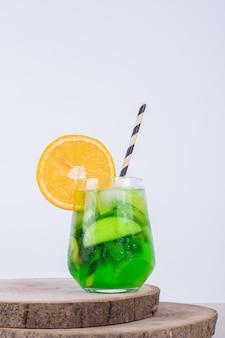 Szklanka soku z kawałkami owoców na białej ścianie.