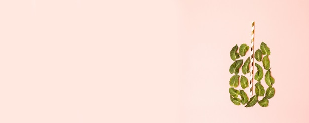 Szklanka soku z liści mięty i słomy na jasnoróżowym