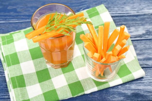 Szklanka soku z marchwi z plastrami warzyw na stole