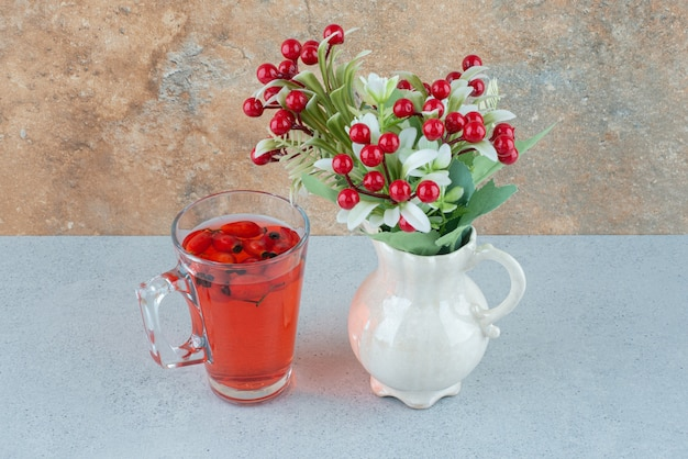 Szklanka soku z owoców dzikiej róży i sztucznych kwiatów na niebieskim stole. zdjęcie wysokiej jakości