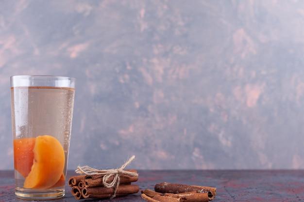 Szklanka soku z plastrami gruszki i laskami cynamonu na tle marmuru.